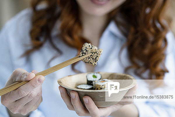 Woman's hands holding bowl and chopsticks with sushi  close-up