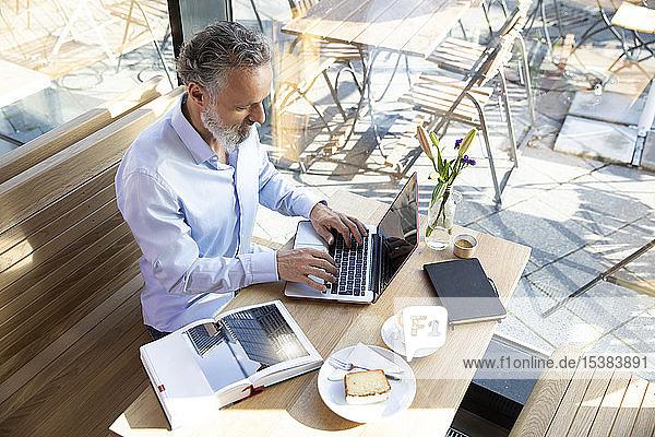 Reifer Mann mit Laptop in einem Café mit Buch auf dem Tisch