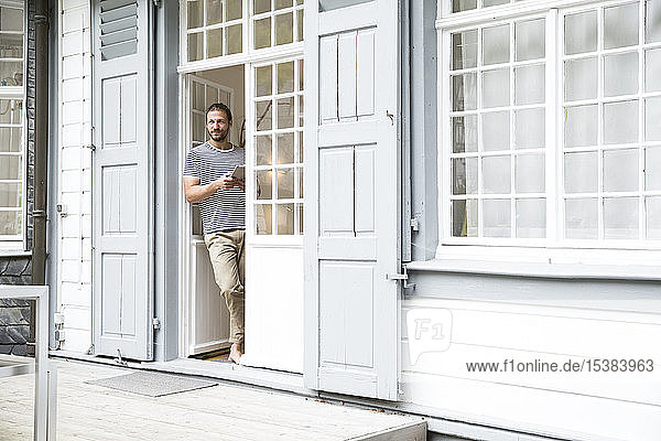 Junger Mann mit Tablette steht zu Hause an der Terrassentür