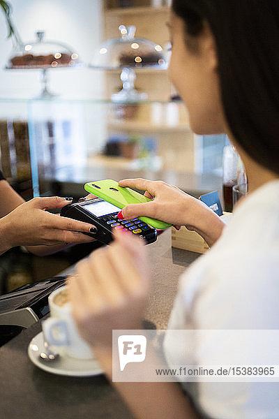 Nahaufnahme eines bargeldlos mit Smartphone zahlenden Kunden in einem Cafe