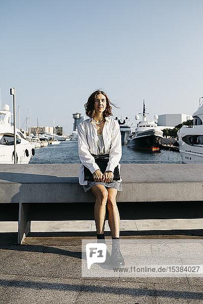 Hübsche Geschäftsfrau sitzt nach der Arbeit am Yachthafen und entspannt sich