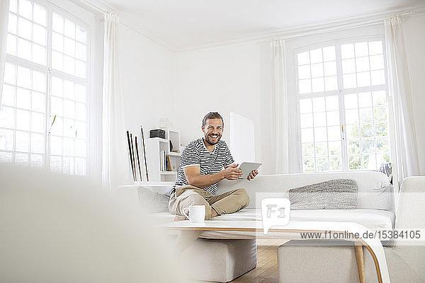 Glücklicher junger Mann sitzt zu Hause auf der Couch und hält Tablette
