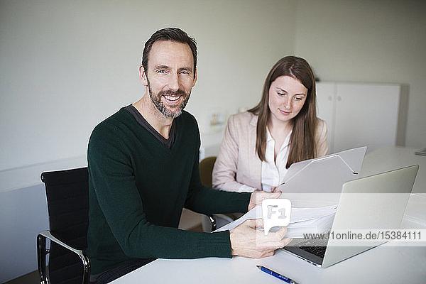 Porträt eines lächelnden Geschäftsmannes und Mitarbeiters  der am Schreibtisch im Büro arbeitet