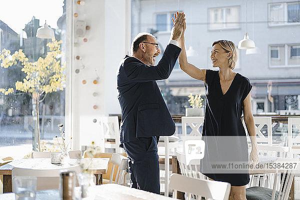 Erfolgreicher Geschäftsmann und erfolgreiche Geschäftsfrau geben sich in einem Café die Klinke in die Hand