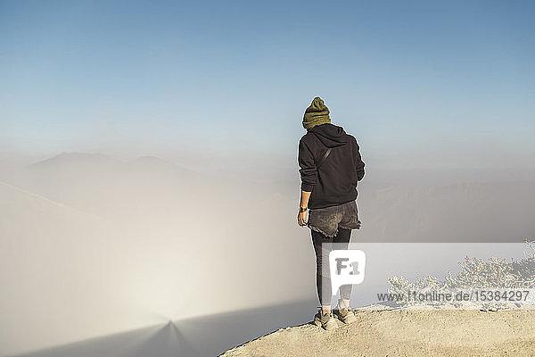 Junge Frau steht am Rande des Vulkans Ijen  Java  Indonesien