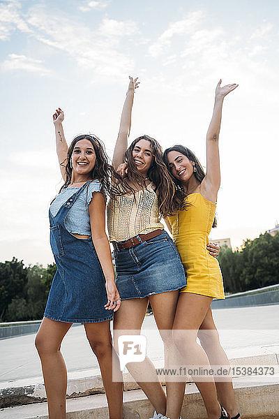 Drei glückliche Freundinnen posieren im Freien
