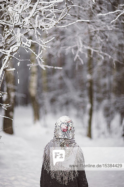 Back view of little girl wearing headscarf standing in front of winter forest