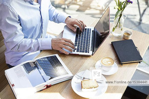 Nahaufnahme eines Mannes mit Laptop in einem Cafe mit einem Buch auf dem Tisch