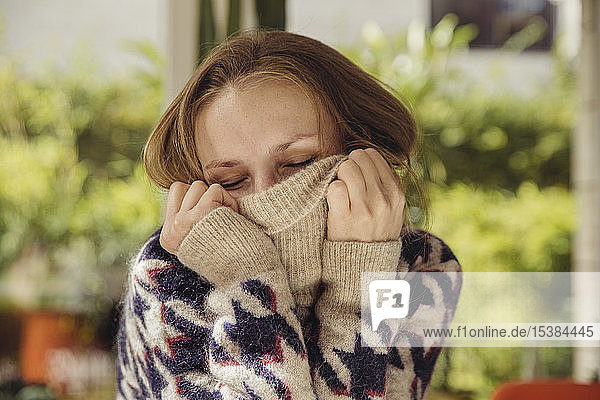 Portrait of young woman with closed eyes sinking in her woolen sweater