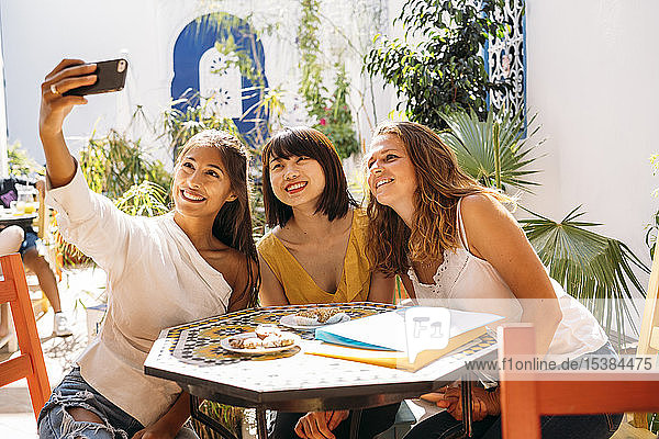Three happy female friends meeting in a cafe taking a selfie