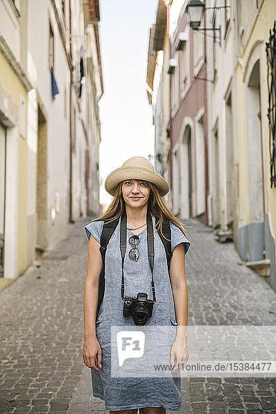 Porträt einer Frau mit Kamera in einer Gasse in der Altstadt von Coimbra  Portugal