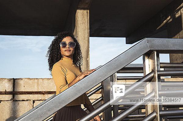 Schöne Frau,  trägt Sonnenbrille,  steht auf einer Treppe