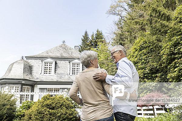 Rückansicht eines älteren Ehepaares  das im Garten seines Hauses steht