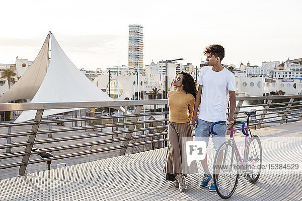 Junges Paar mit Fahrrad  zu Fuß in der Stadt Junges Paar mit Fahrrad, zu Fuß in der Stadt