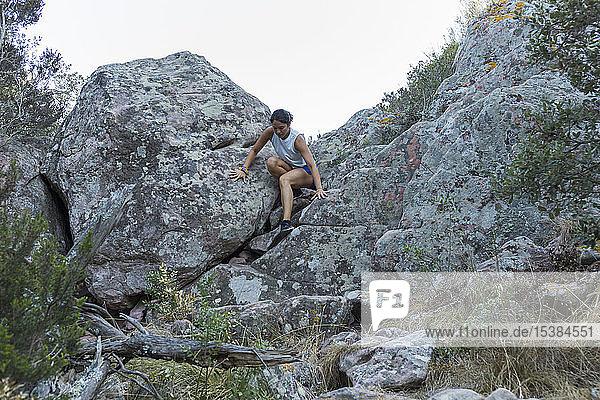 Junge Asiatin klettert in einer Felswand