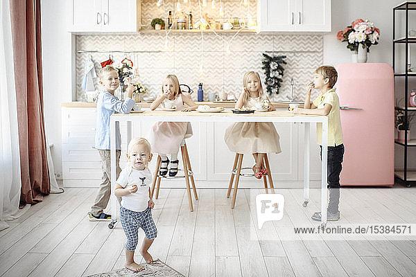 Fivechildren eating cookies in the kitchen