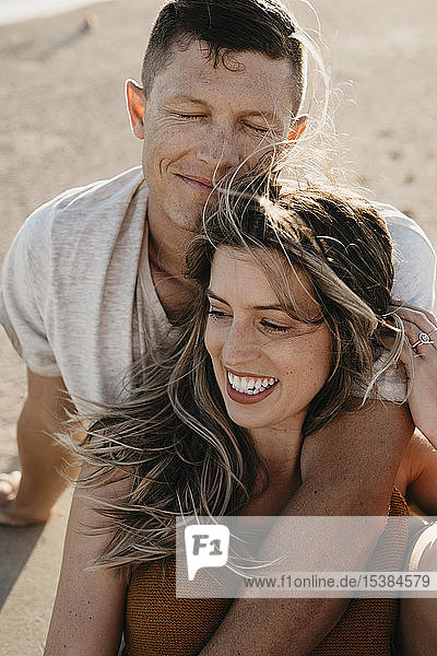 Glückliches  anhängliches junges Paar am Strand