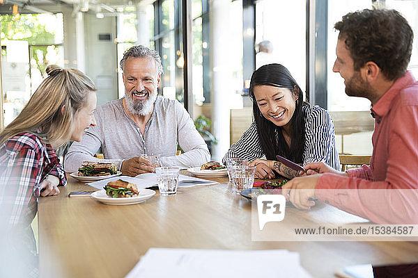 Fröhliche  ungezwungene Geschäftsleute beim Geschäftsessen in einem Cafe