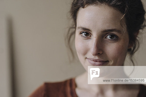 Porträt einer lächelnden jungen Frau mit braunen Haaren und Augen