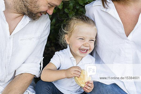 Glückliches kleines Mädchen mit einem Imbiss inmitten der Eltern
