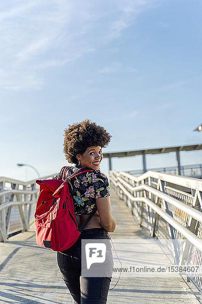 Weibliche Afroamerikanerin mit Kopfhörern und Smartphone beim Musikhören