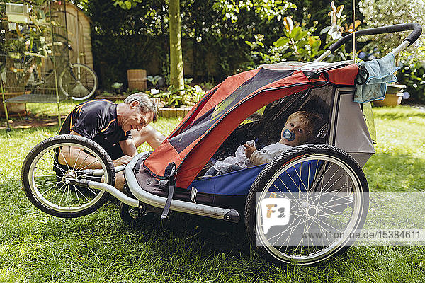 Father repairing bicycle trailer with baby boy sitting in it