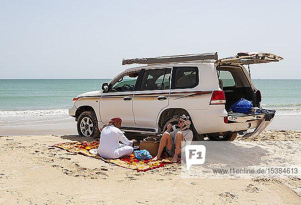 Tourist bei einer Kaffeepause mit seinem einheimischen Fahrer am Indischen Ozean  Oman