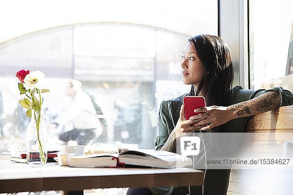 Frau mit Ohrstöpseln und Handy in einem Cafe