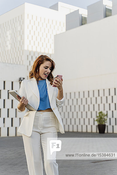Businesswoman in white pant suit  carrying laptop  using smartphone