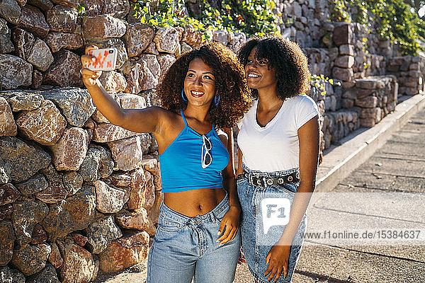 Porträt von zwei jungen Frauen  die sich mit einem Smartphone selbstständig machen