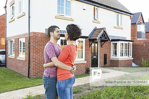 Glückliches Paar umarmt sich vor ihrem neuen Zuhause
