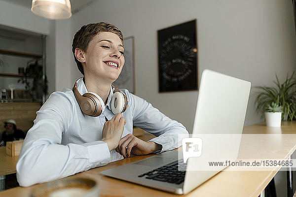 Happy businesswoman with laptop and headphones in a cafe