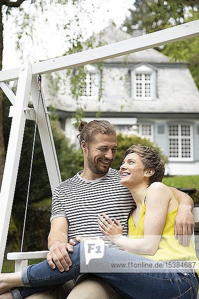 Glückliches  entspanntes Paar im Garten ihres Hauses