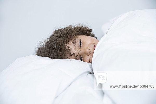 Bildnis eines im Bett liegenden Jungen mit lockigem Haar