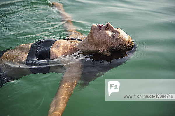 Mature woman floating in a lake with closed eyes
