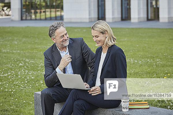 Geschäftsfrau und Geschäftsmann sitzen mit Laptop an einer Wand in der Stadt