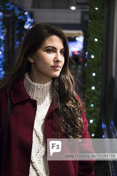 Porträt einer jungen Frau  die in ein Schaufenster schaut
