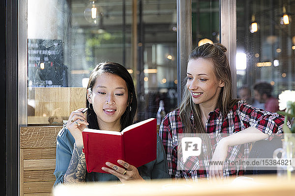 Two women with book in a cafe