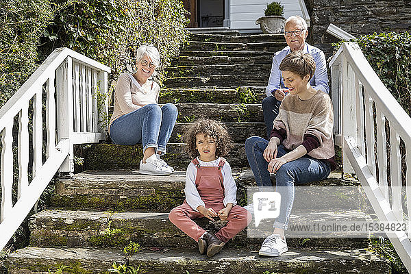 Senior couple with adult daughter and grandson sitting on stairs in garden of their home