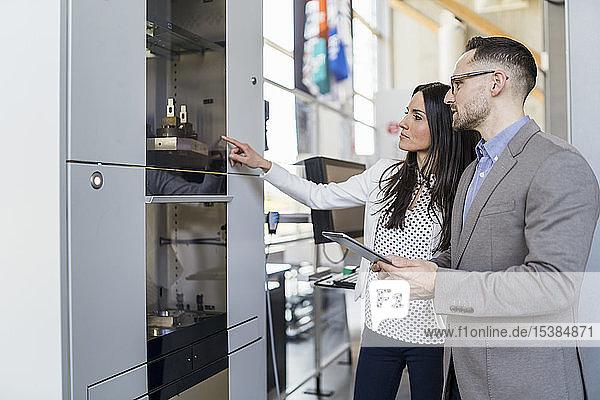 Geschäftsmann und Geschäftsfrau im Gespräch an einer Maschine in einer modernen Fabrik