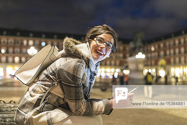 Spanien  Madrid  Plaza Mayor  glückliche junge Frau mit ihrem Smartphone