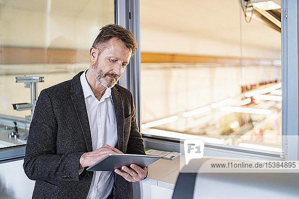 Geschäftsmann mit Tablett am Fenster mit Fabrikhintergrund