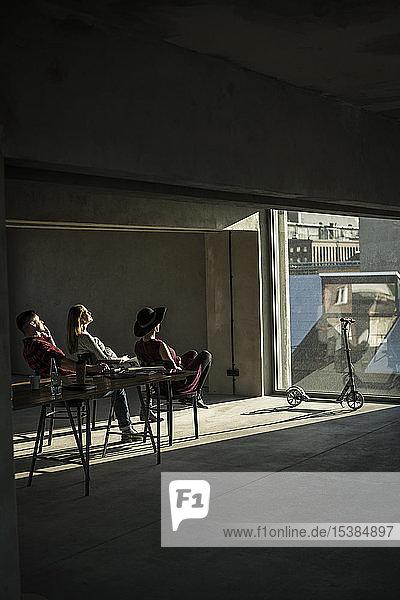 Gruppe von Kreativen  die in ihrem Büro sitzen  aus dem Fenster schauen und die Sonne genießen