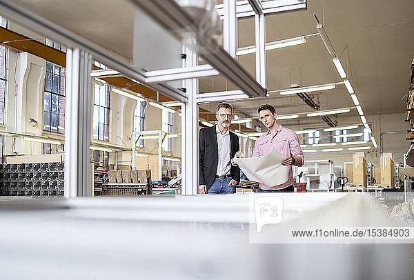 Zwei Männer mit Plan in einer Fabrik