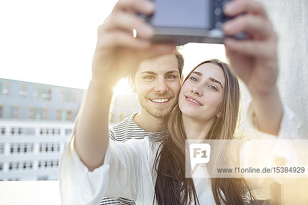 Smiling young couple taking a selfie outdoors