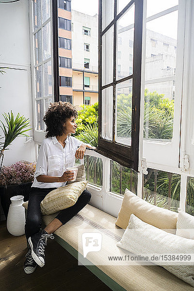 Beautiful woman sitting on bench  looking out of window  drinking coffee