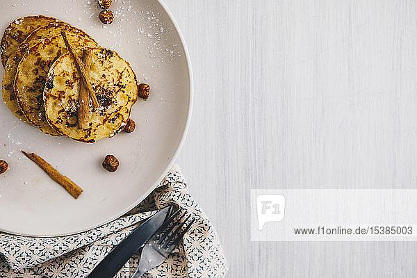 Palatschinken auf Teller mit Haselnüssen  Zimtstangen und Puderzucker