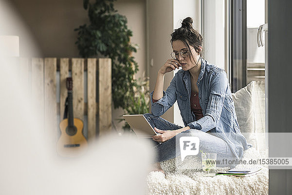 Woman sitting at the window at home using laptop