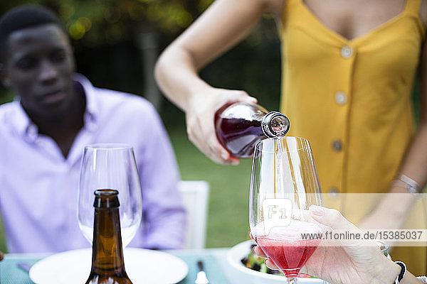 Gastgeber gießt Wein in Gläser bei einem sommerlichen Abendessen im Garten