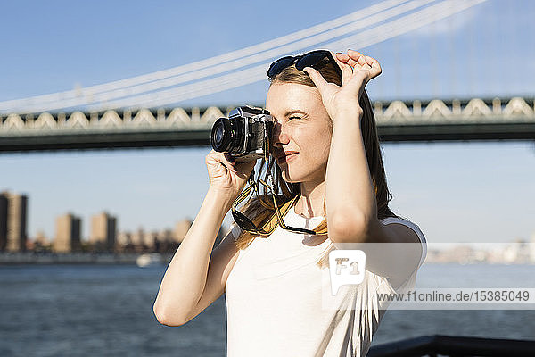 Young woman exploring New York City  taking pictures at Brooklyn Bridge